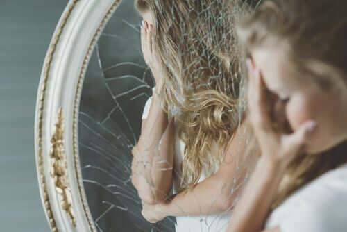 Kvinna framför söndrig spegel.