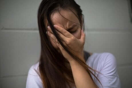 En kvinna med handen för ansiktet känner sig extremt bedrövad för att hon upplevet närvaron av ett spöke.