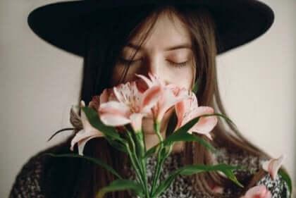 Kvinna som luktar på blommor.
