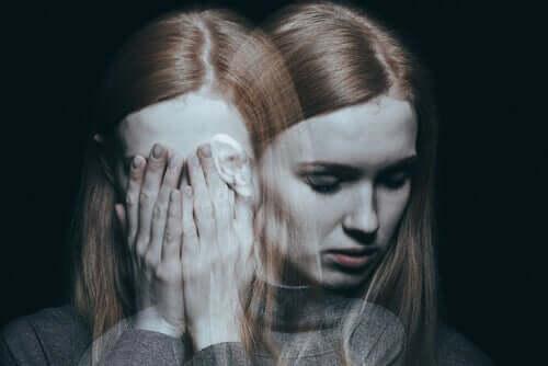 En kluven kvinna med händerna för ansiktet och en spegelbild av henne som ser ledsen ut.