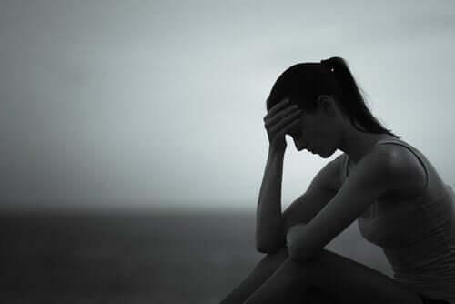 Sexismen i det moderna samhället gör att en kvinna känner sig överväldigad när hon sitter på marken med handen på pannan.
