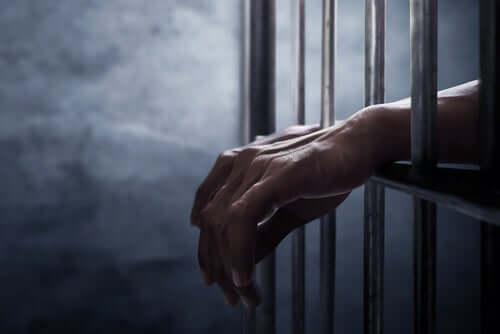 Person bakom galler.