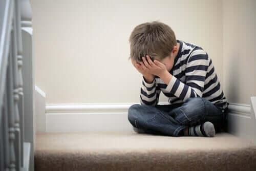 En pojke med skolfobi som sitter på trappan i sitt hem och gråter.
