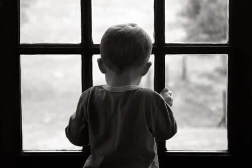 En liten ledsen pojke tittar ut genom fönstret.