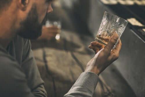 En man tittar på sin drink medan han överväger behandling för alkoholism.