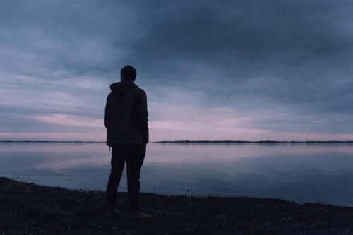 Man som står vid sjö.
