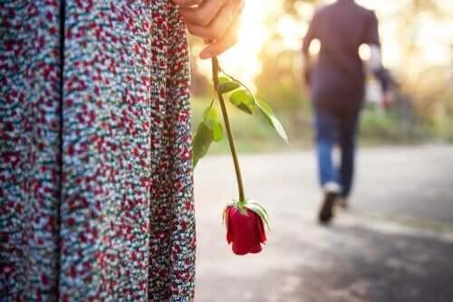Kvinna som håller i en ros.