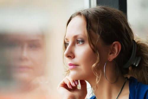 Kvinna som tittar ut genom fönstret.