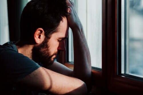 Man som sitter vid fönster.