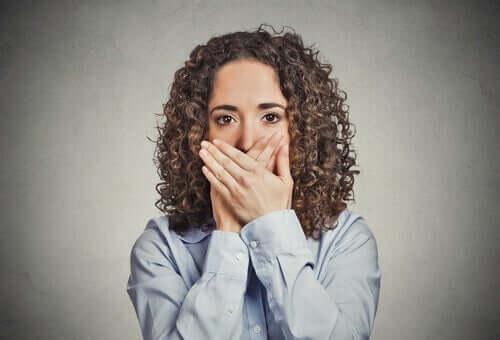 Kvinna med händerna framför munnen.