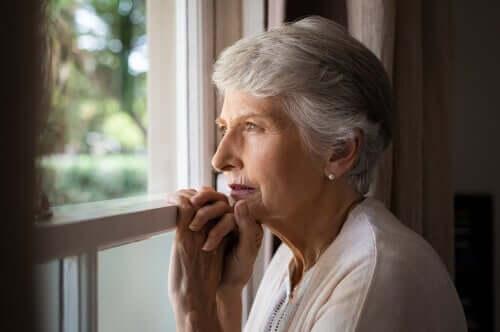 Kvinna som tittar ut genom fönster.