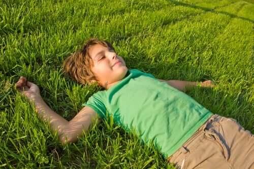 Pojke ligger i gräset