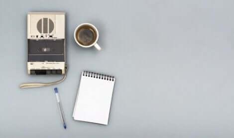 En inspelare bredvid en kopp kaffe, ett skrivblock och en penna.