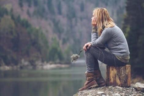 En kvinna funderar vid flodstranden.