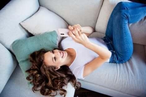 En kvinna som ser med glädje på sin telefon