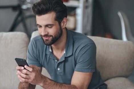En man som läser något trevligt på sin telefon