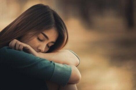 En kvinna med huvudet på armarna och stängda ögon