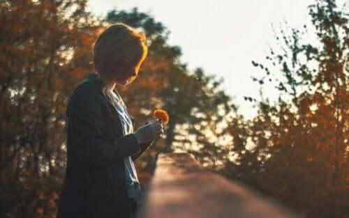 En kvinna som tittar på en blomma