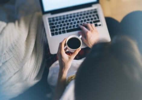En kvinna som dricker kaffe och arbetar på sin dator