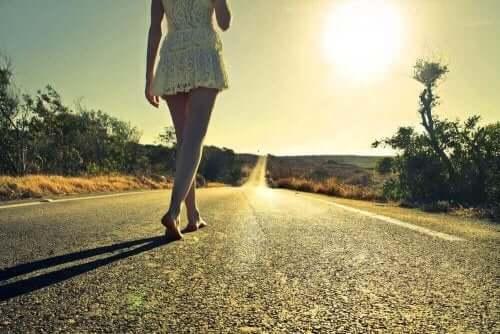 En kvinna följer en lång, enslig väg barforta mot gryningens solsken