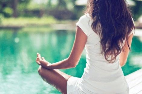 En kvinna som mediterar vid en simbassäng