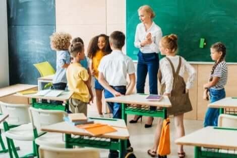 En kvinna som pratar med en grupp barn i ett klassrum