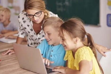 En kvinna som tittar över två barns axlar