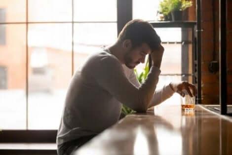 En man som dricker whiskey i en förövrigt tom bar