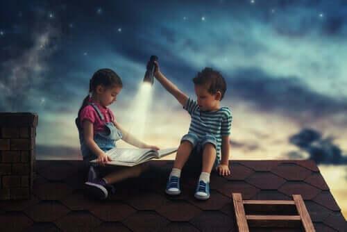 En pojke håller en ficklampa så att en flicka kan läsa en bok på ett tak