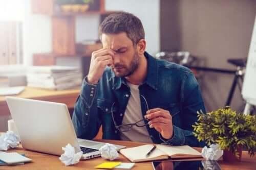 En man känner sig stressad när han arbetar