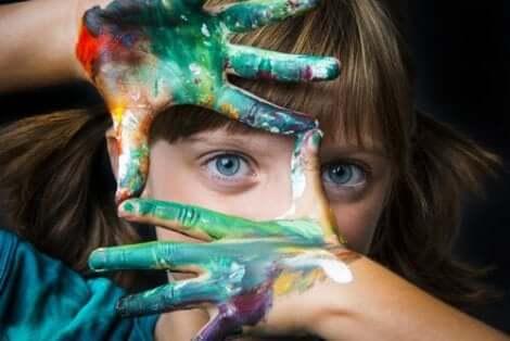 En liten flicka med målade händer som inramar hennes öga