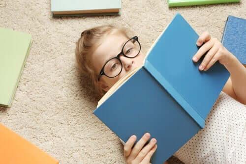 En flicka som ligger på golvet och läser