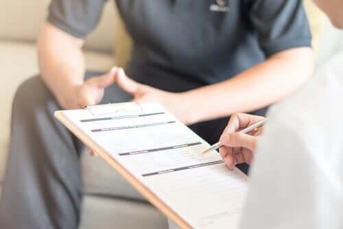 En terapeut som fyller i en patients kliniska historia innan han utför nidoterapi.