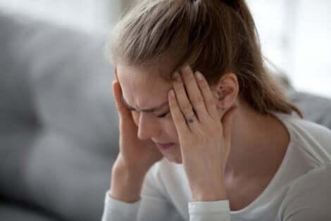 En kvinna som behöver hantera fysisk smärta från huvudvärk