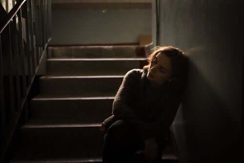 En ledsen kvinna lutad mot väggen i en trappuppgång