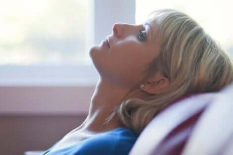 En kvinna som lutar sig tillbaka på en soffa.