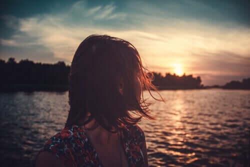 En kvinna som ser på en sjö.