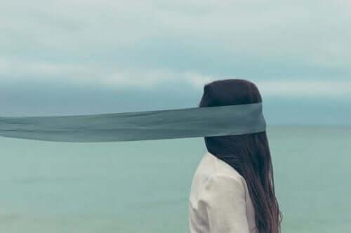 En kvinna som står framför havet i gråmulet väder med en lång halsduk över ögonen