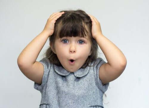 En liten flicka med händerna på huvudet ser förvånad ut