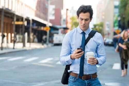 En man som går på gatan och tittar på sin mobiltelefon