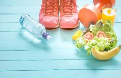 Hälsosam mat, tennisskor, en hantel och en flaska vatten på ett blått golv