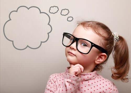 En ung flicka med glasögon med en tankebubbla målad på väggen bredvid henne