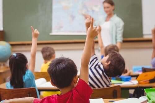 Barn i skolan räcker upp handen