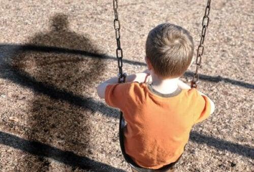 Ledsen pojke som sitter på gungan på grund av emotionell försummelse av barn hemma