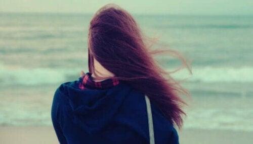 Flicka som ser ut över havet tänker på att be om hjälp