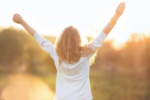 Kvinna i soljus med lyfta armar