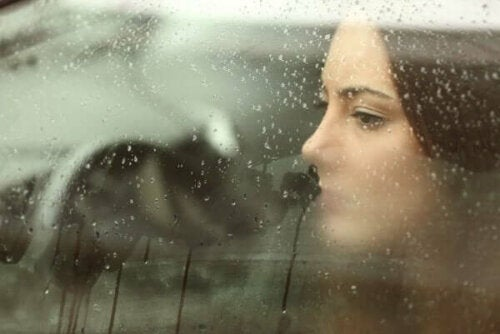Kvinna som tittar ut genom bilfönstret med emotionellt resonerande för att tänka på någon långt borta