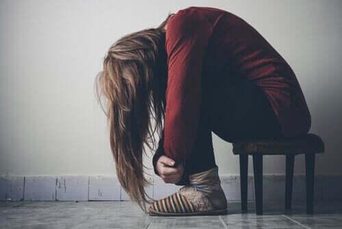 Deprimerad kvinna hukad på pall