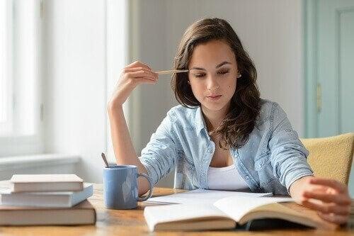 Tjej läser en bok och studerar med kaffe