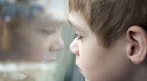 Ledsen pojke, vid fönster, som lider av övergrepp, en av orsakerna bakom narcissistisk personlighetsstörning